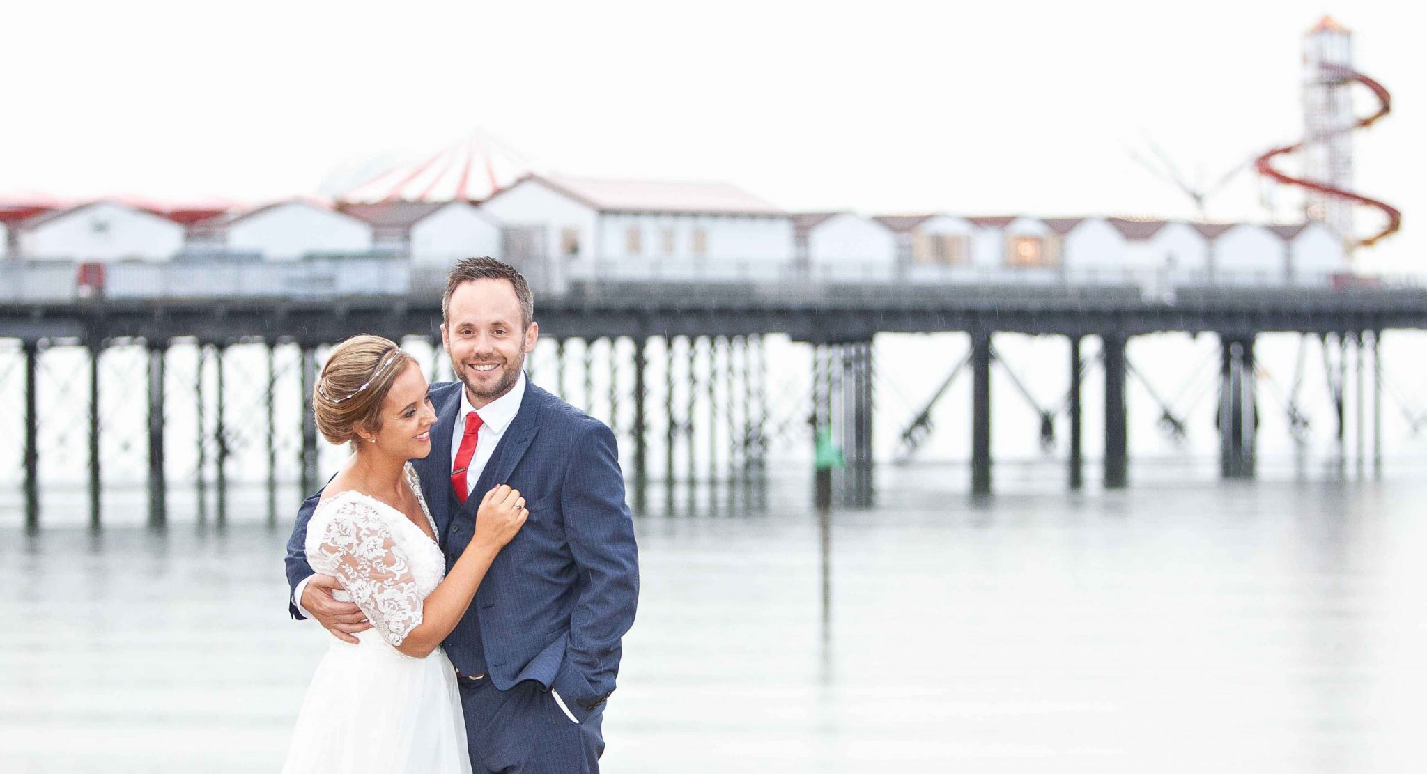 bride and groom portrait in rain on Herne bay beach in front of pier