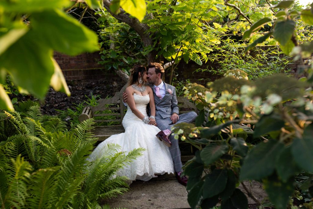 bride and groom sitting on bench surrounded by foilage and plants