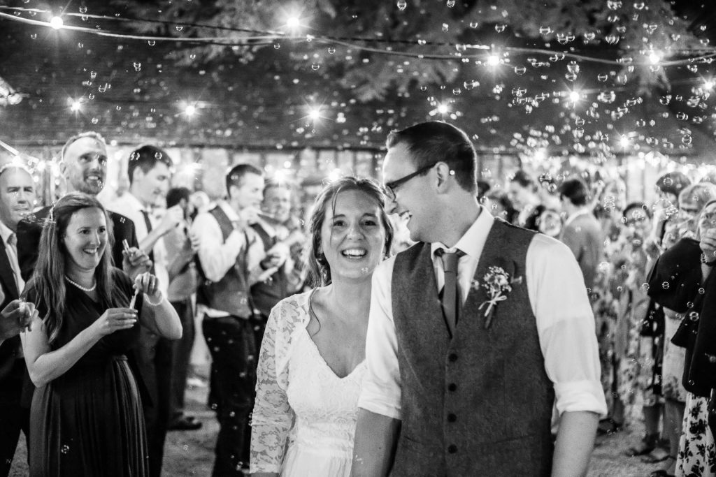 bride and groom bubble exit at night outside under lights