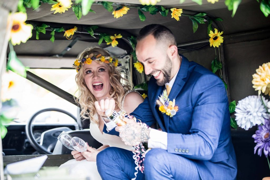 bride and groom smiling with champagne in Land rover car