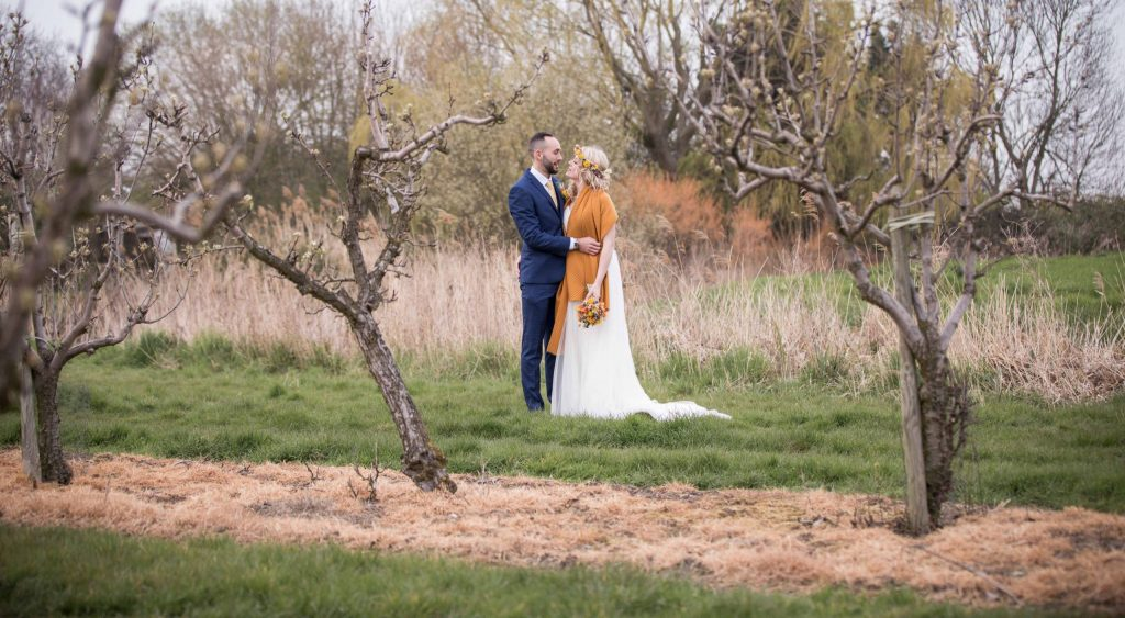 bride and groom portrait in orchard