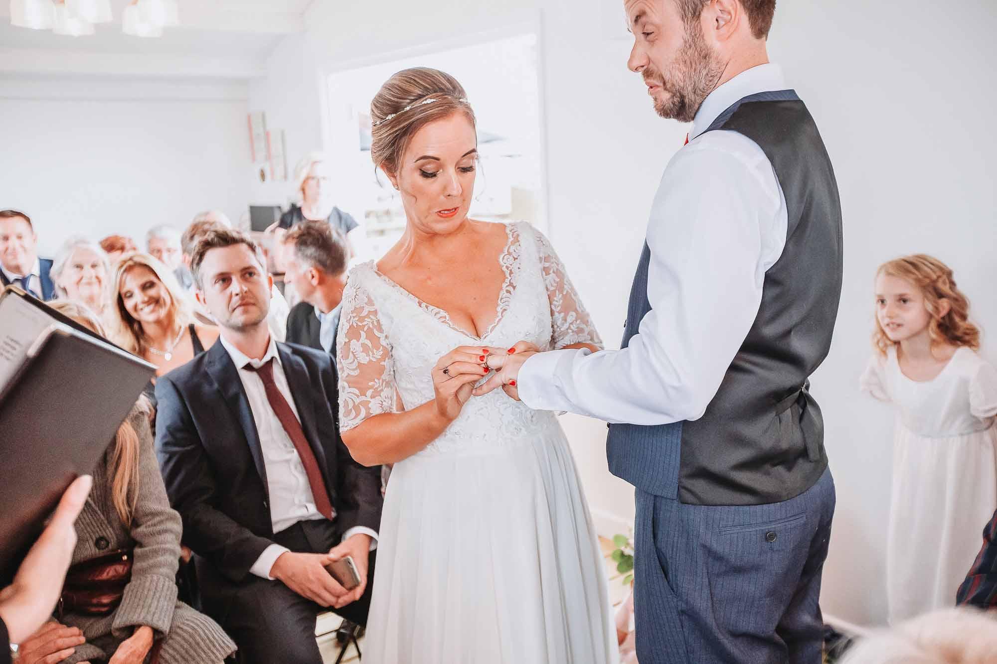bride struggling to get wedding band on grooms finger