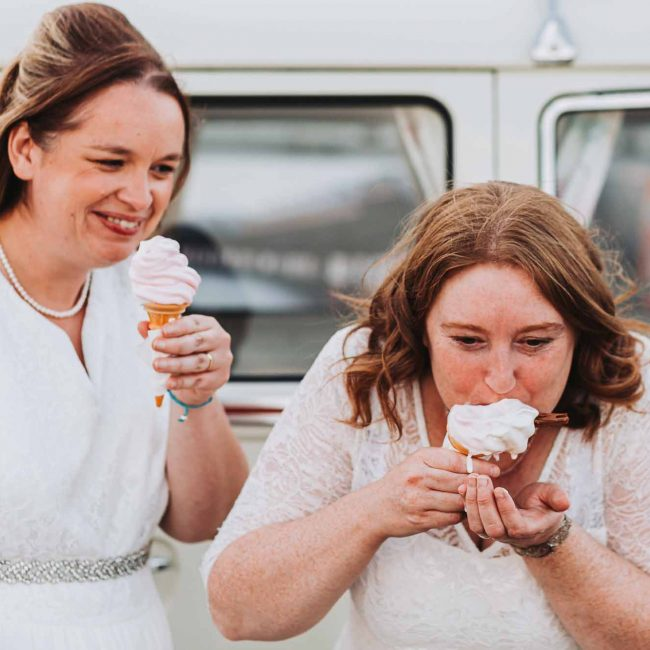 two bride laughing and messily eating ice cream
