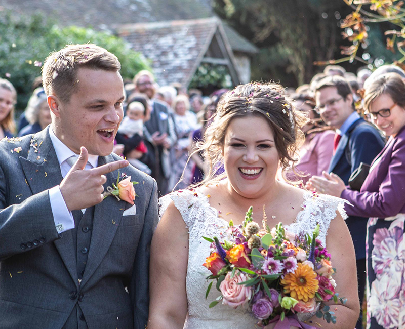 wedding photography in kent couple with confetti and bouquet of flowers