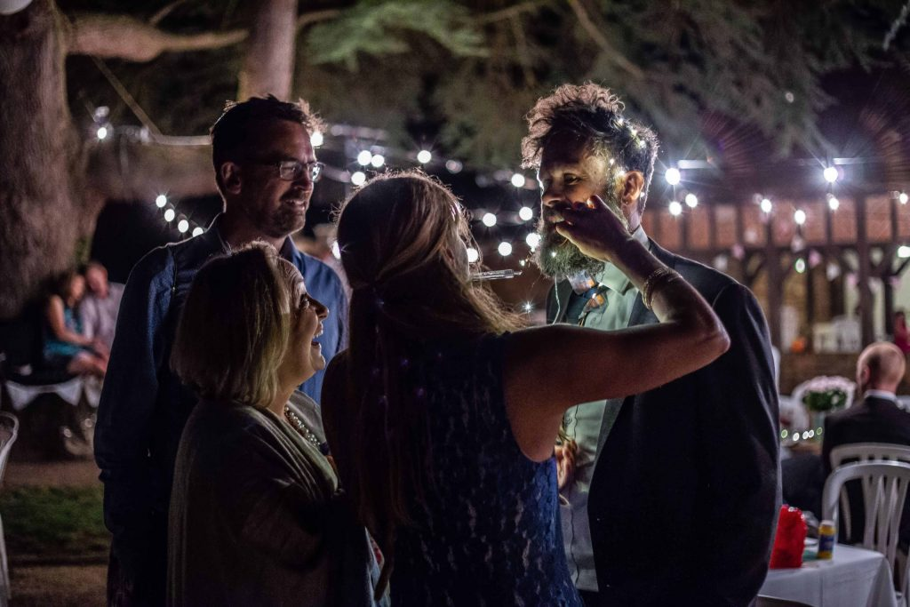 wedding guest having his beard and hair wrapped in fairy lights