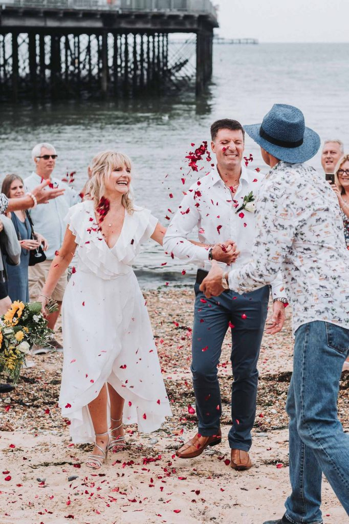 confetti thrown over bride and groom on beach
