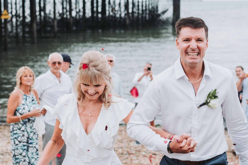 confetti being thrown over bride and groom on beach
