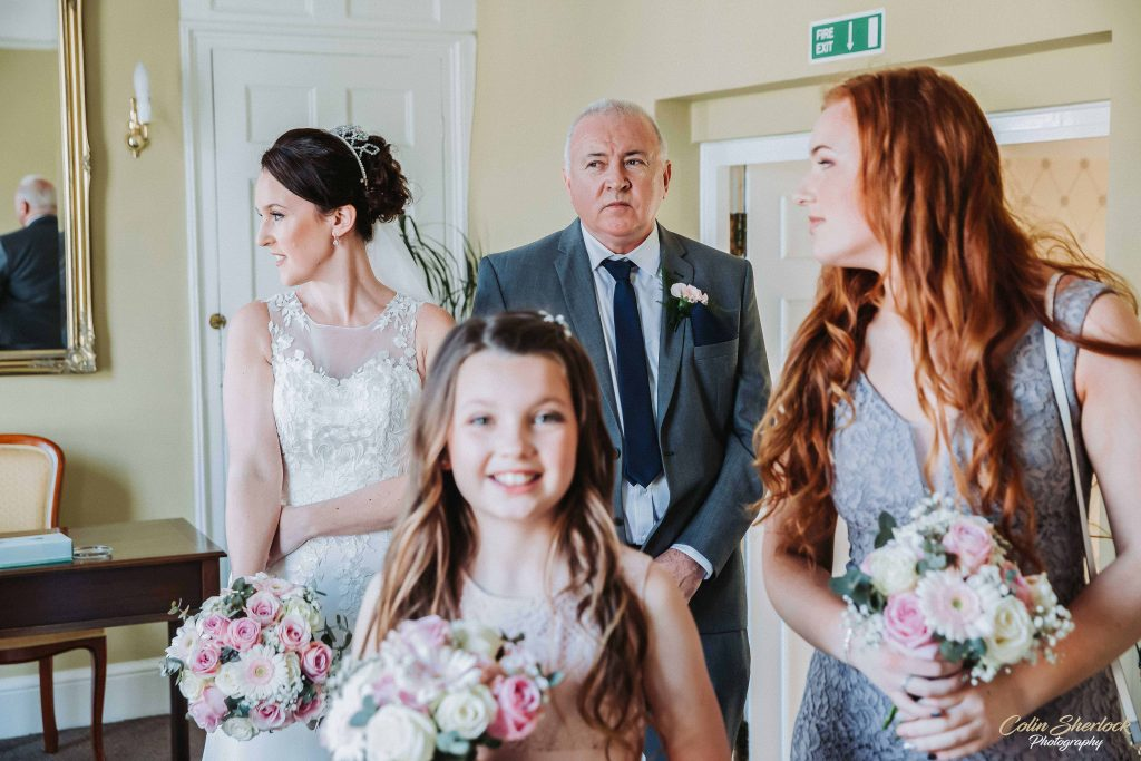 bride waiting to enter wedding ceremony with father and bridesmaids