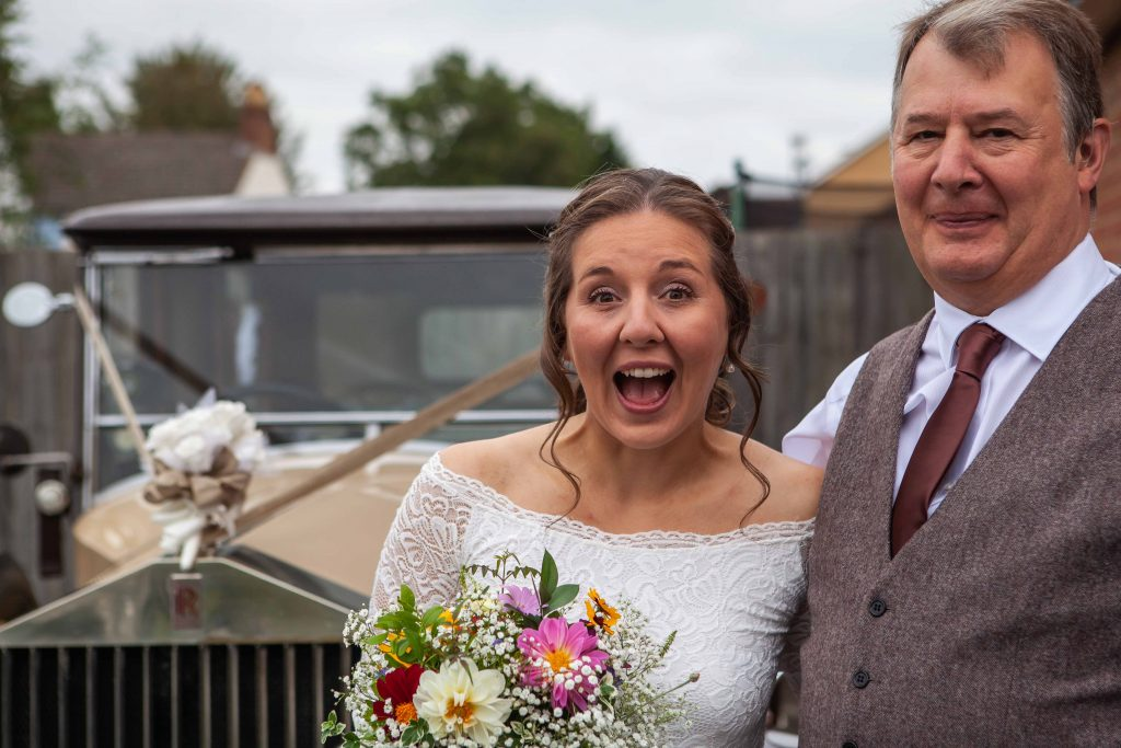 bride with father posing by vintage wedding car