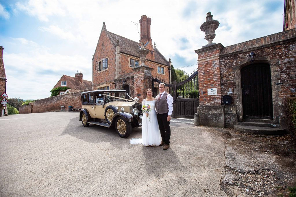 bride and father next to vintage wedding car