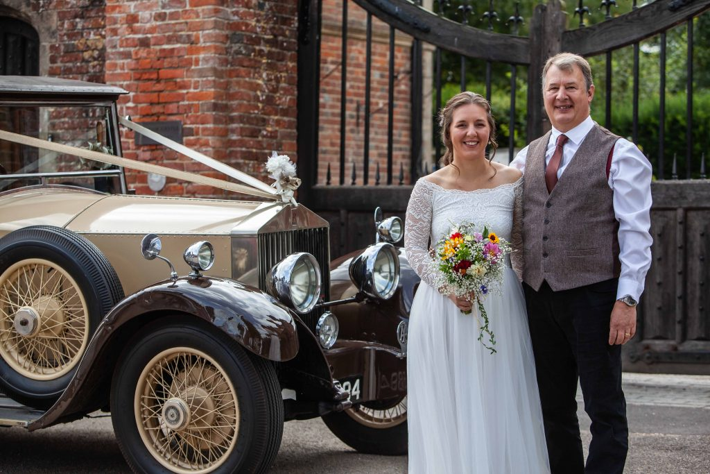 bride and father with vintage wedding car