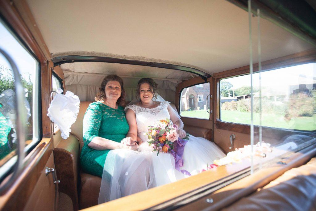 bride with mum in vintage wedding car