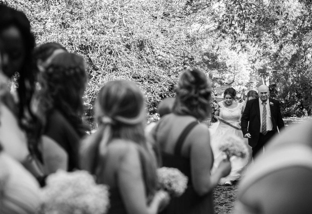 bridesmaids watching bride walk towards them