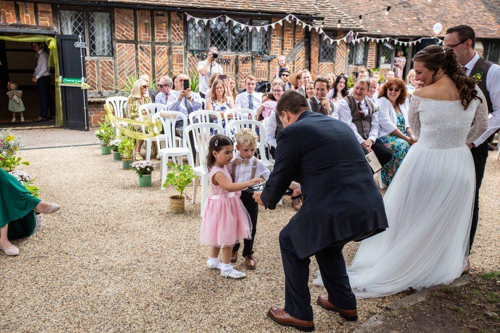 boy and girl handing over rings to wedding Pastor