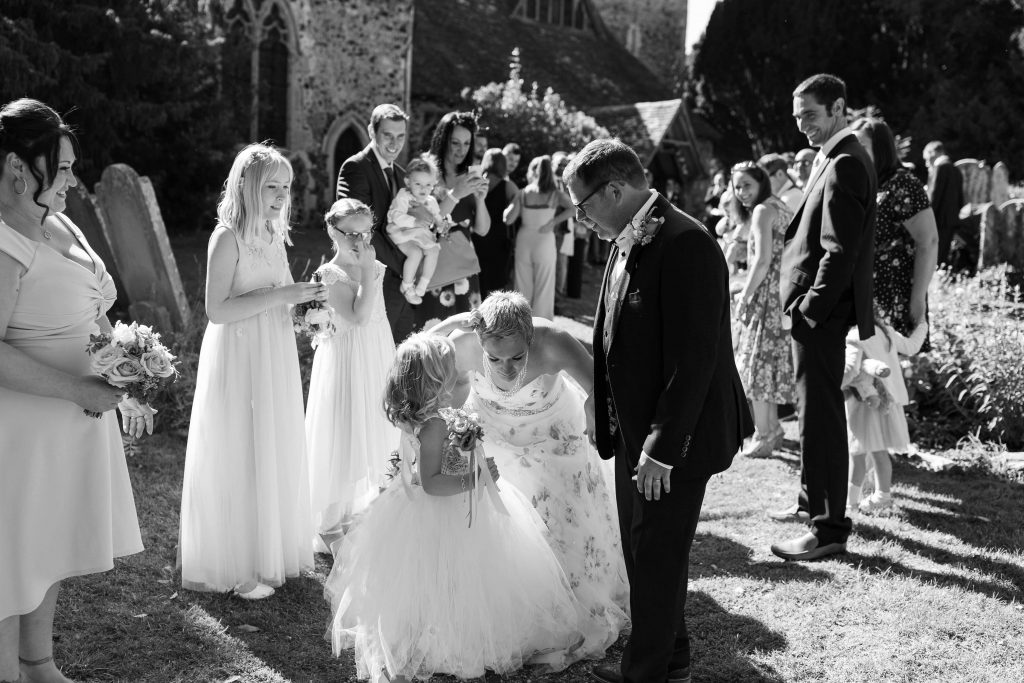 daughter picking confetti out of brides hair
