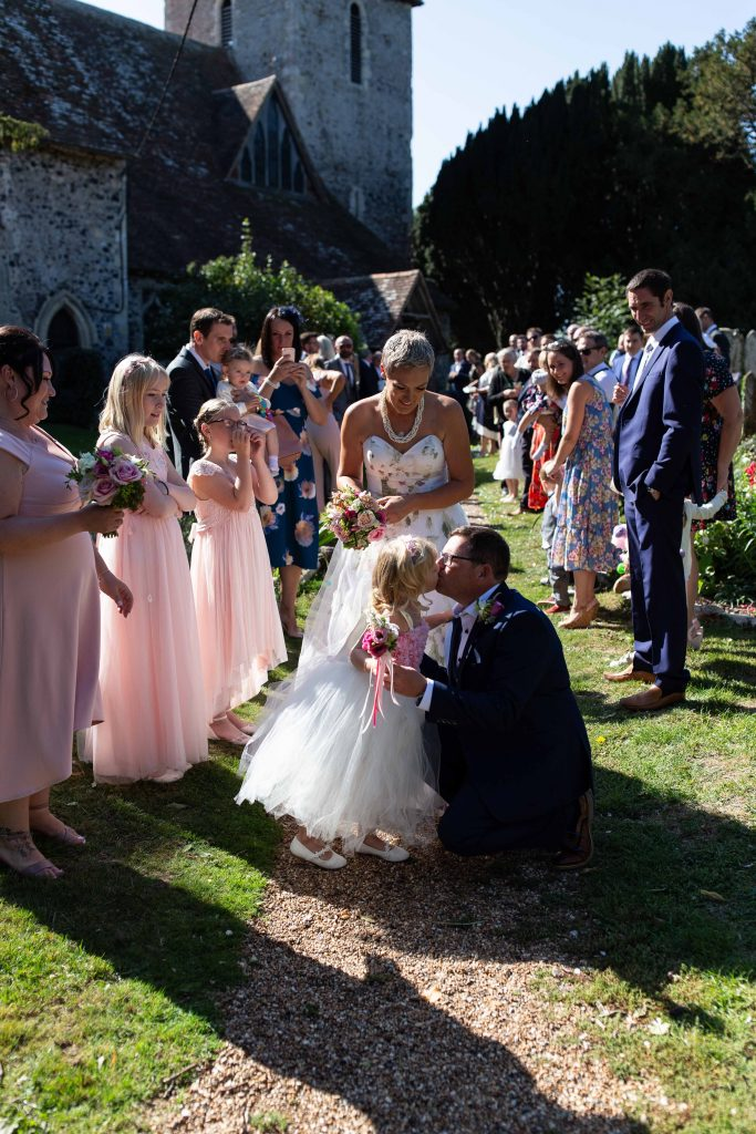 daughter giving groom a kiss