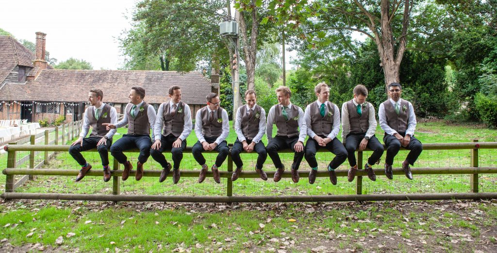 groom and groomsmen on fence at chilham village hall