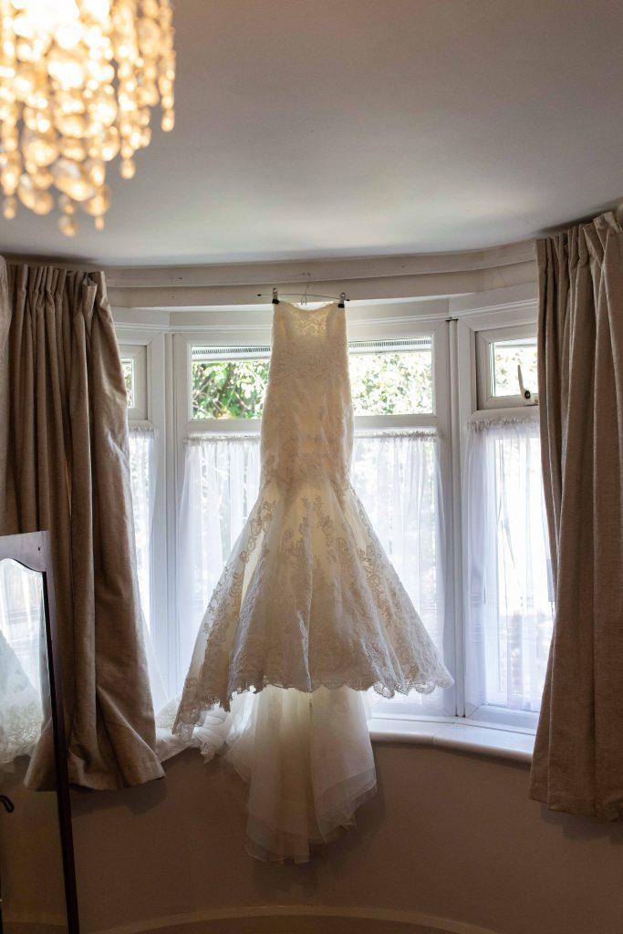 bridal dress hanging in window