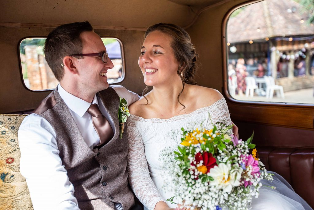 bride and groom in vintage wedding car