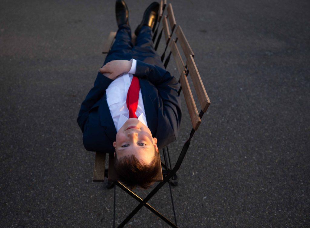 boy lying on seats at wedding looking up at camera