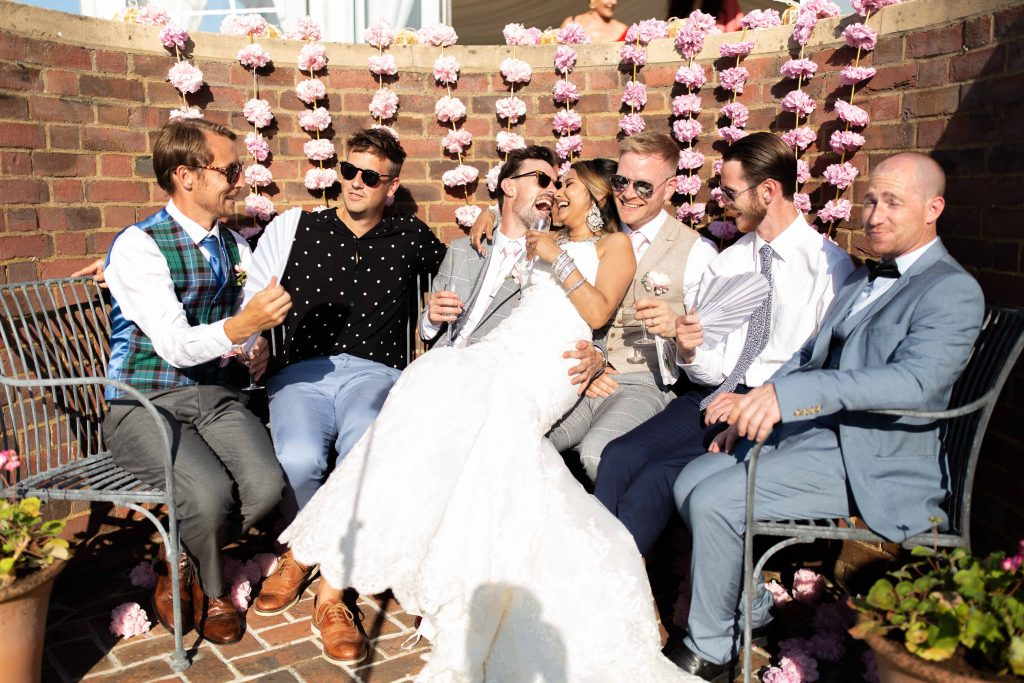 bride and groom with grooms friends laughing
