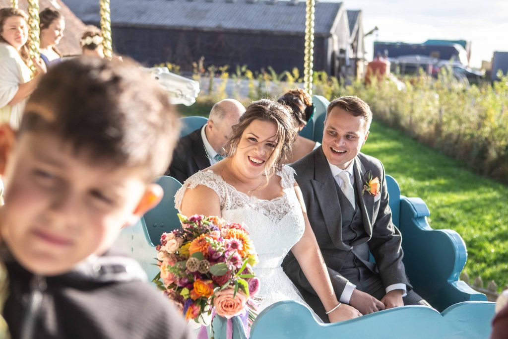 bride and groom on carousel at preston court