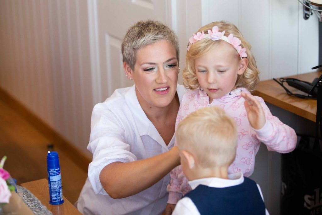 bride with young son and daughter fixing sons hair