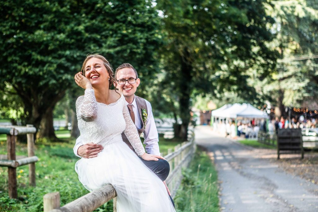 bride and groom sitting on fence for portrait