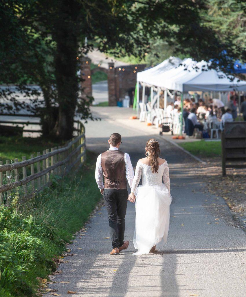 bride and groom walking towards marquee