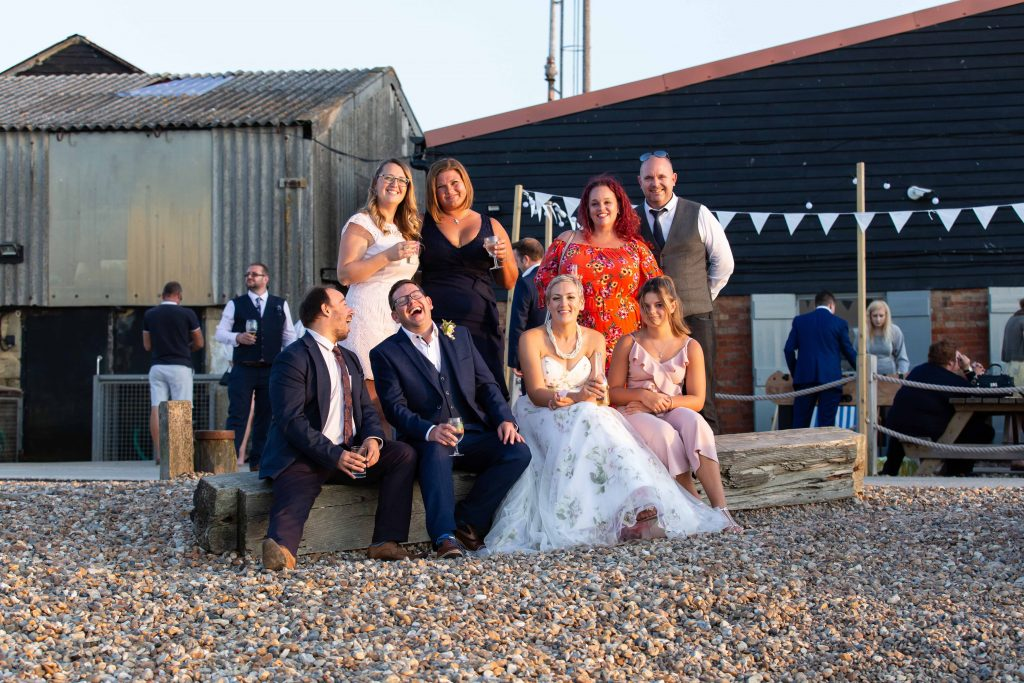 wedding guests with bride and groom on beach