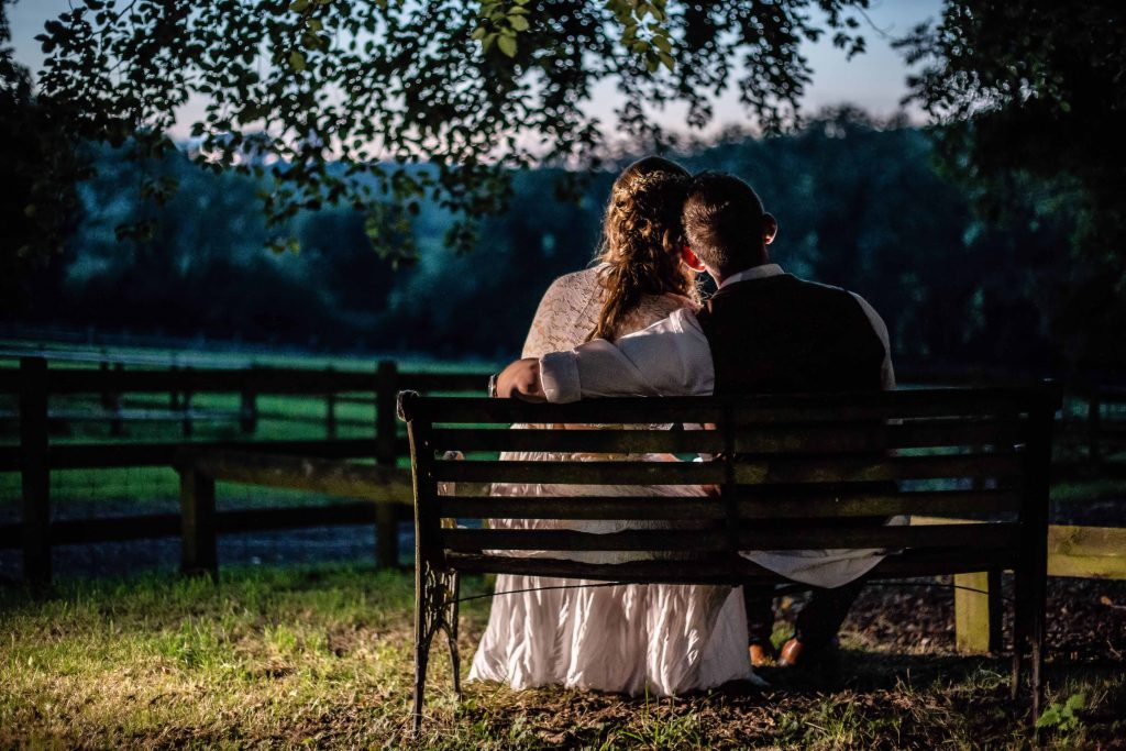 bride and groom on bench looking over fields