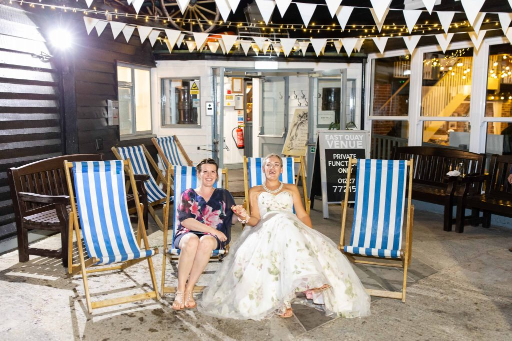 bride with best friend on deckchairs outside East Quay wedding venue