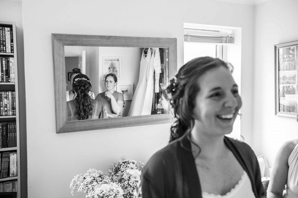 bride an bridesmaids reflected in mirror