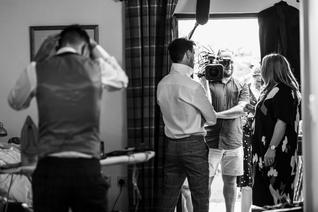 television crew with groom at wedding