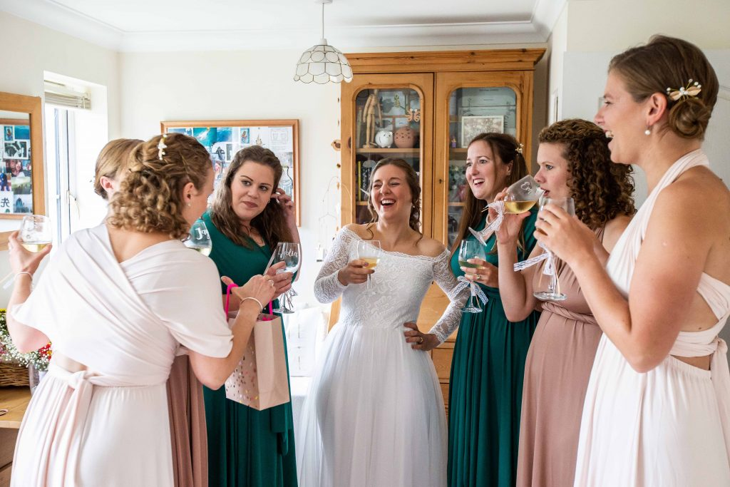 bride and bridesmaids drinking champagne and laughing