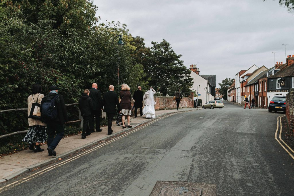 bride and groom with wedding party walking through Canterbury