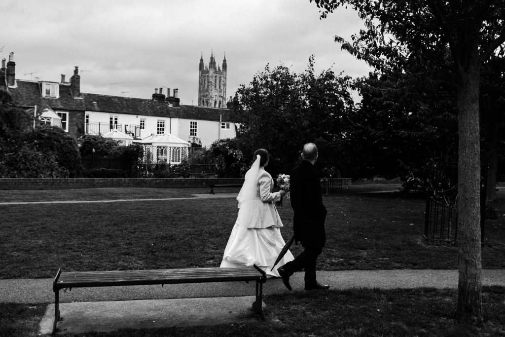 bride and groom walking together looking at Canterbury cathedral in the distance