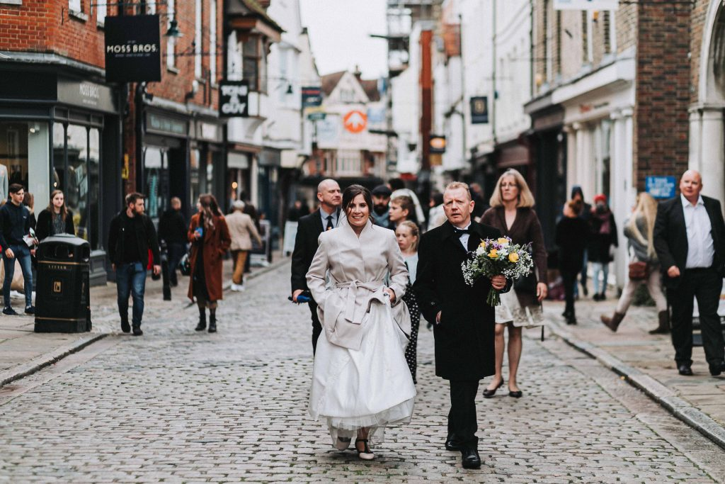 bride and groom walking to wedding venue through streets of Canterbury