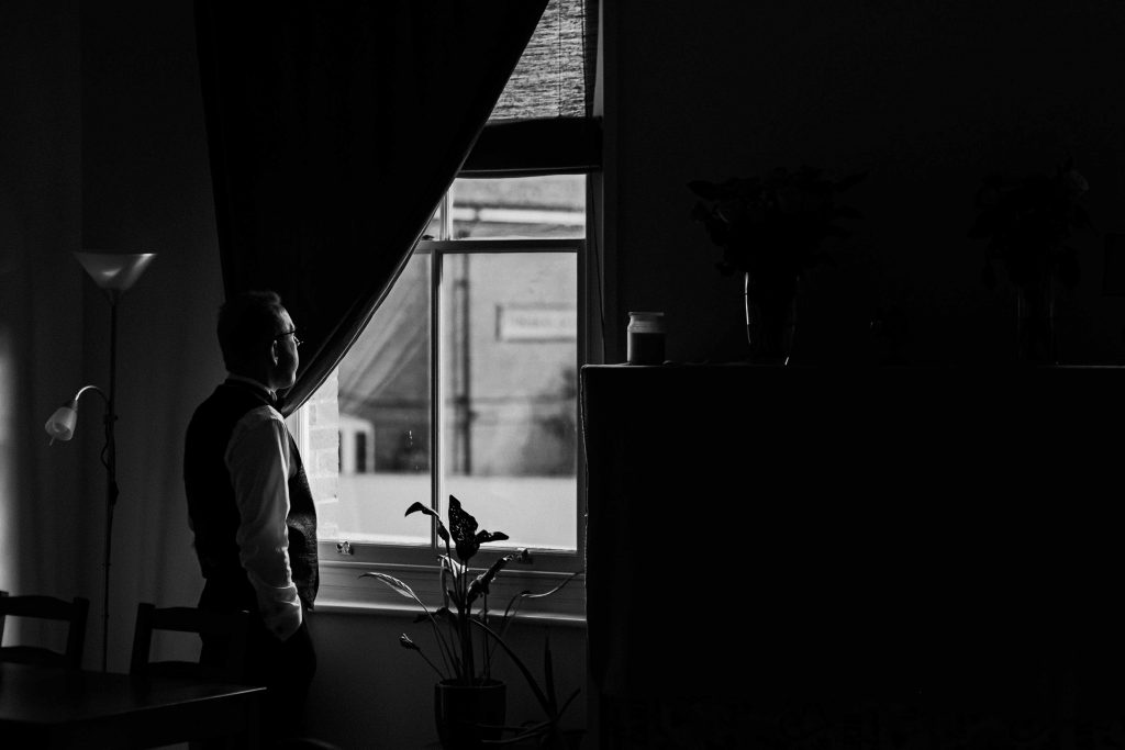 Groom looking out the window in pensive thought