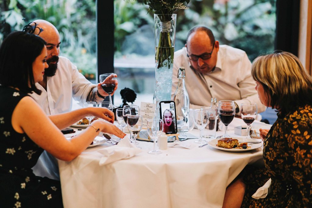 wedding guests and zoom call by phone at wedding