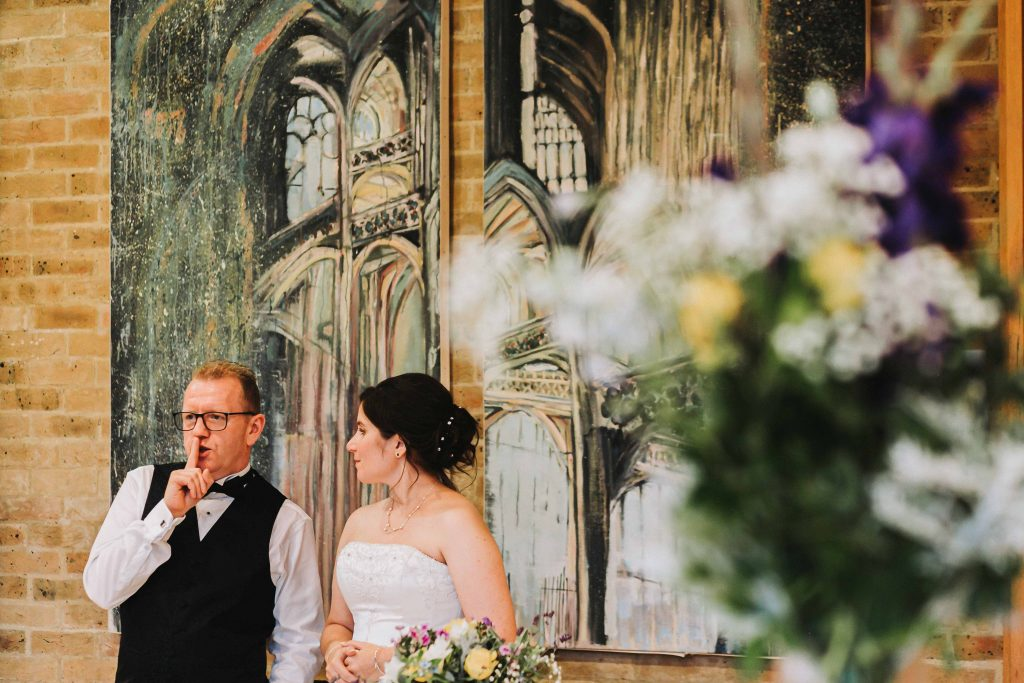 groom silencing guests with his finger to say thank you