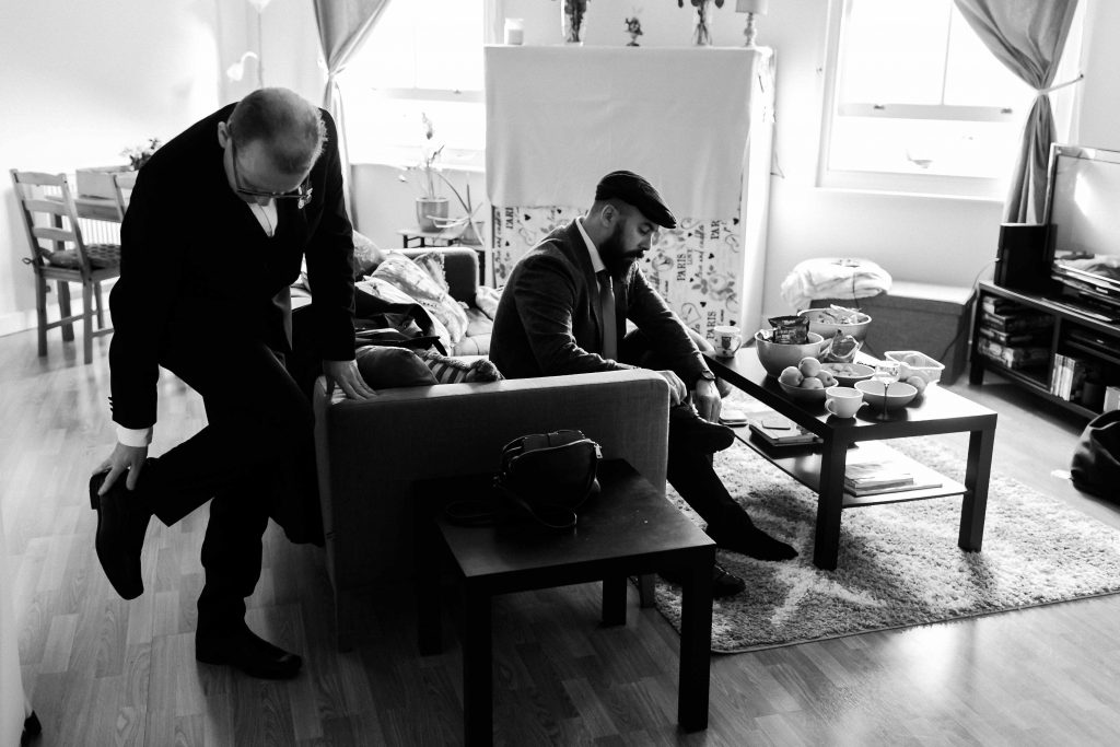 broom and groomsman putting on shoes