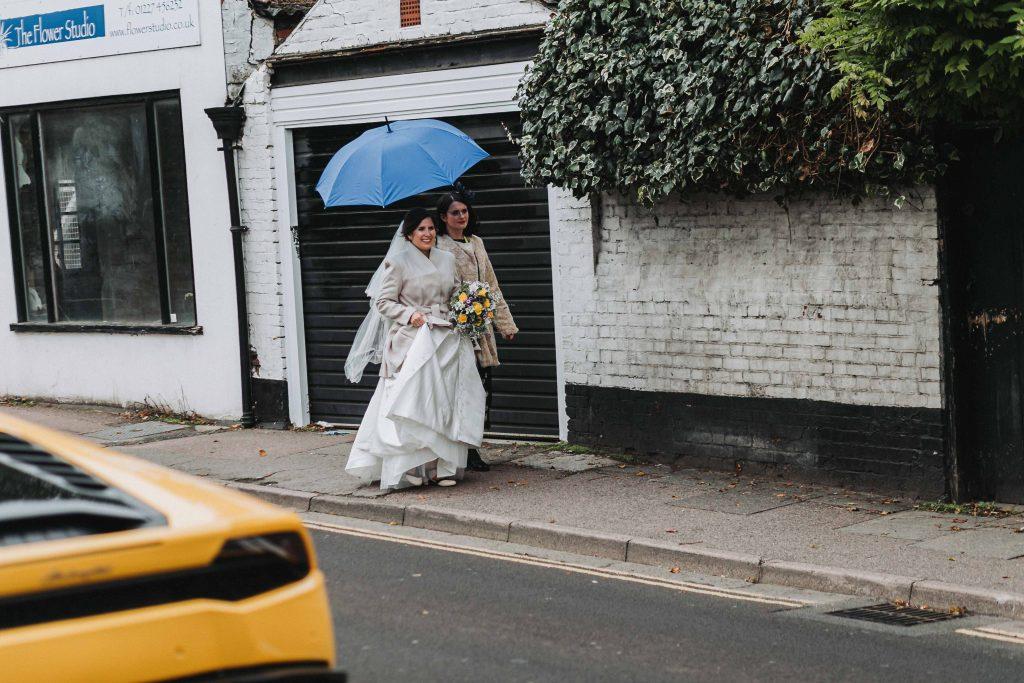 bride with bridesmaid walking with umbrella in rain