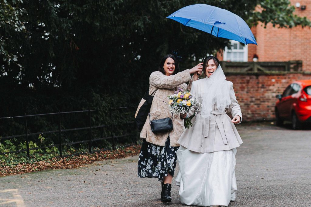 bride with bridesmaid walking with umbrella in rain laughing