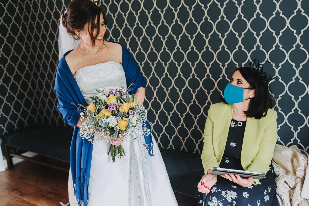 bride with bouquet and bridesmaid with mask in registry office