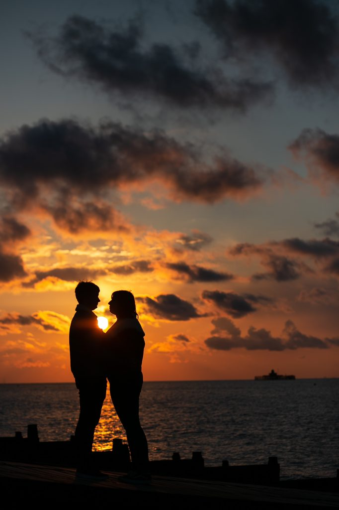 couple silhouette against sunset on the coast