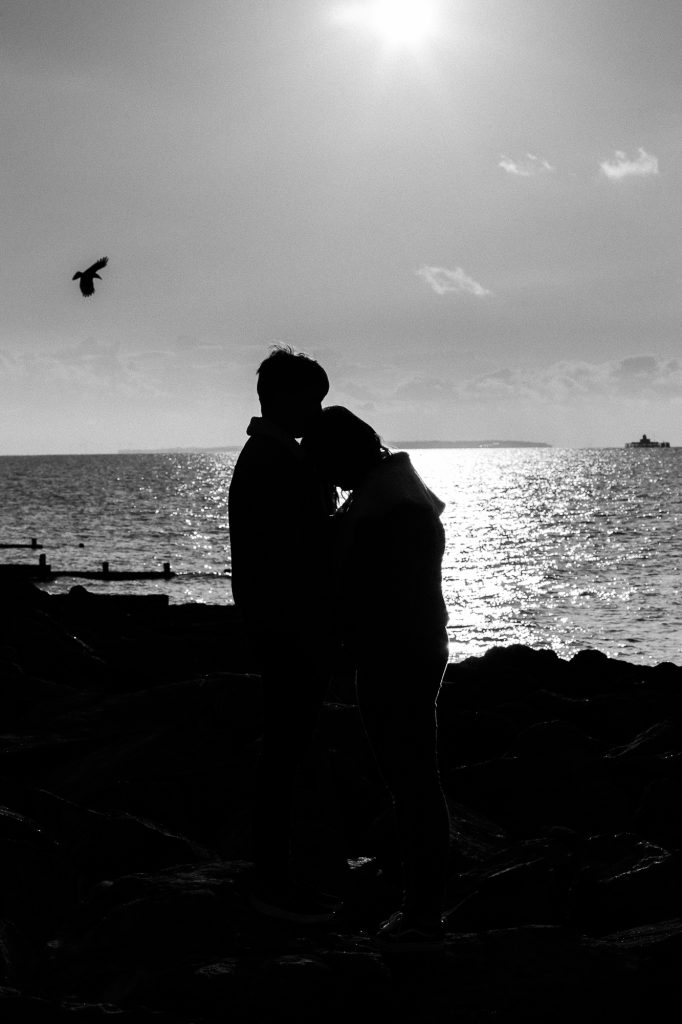 picture of couple silhouetted on beach in black and white