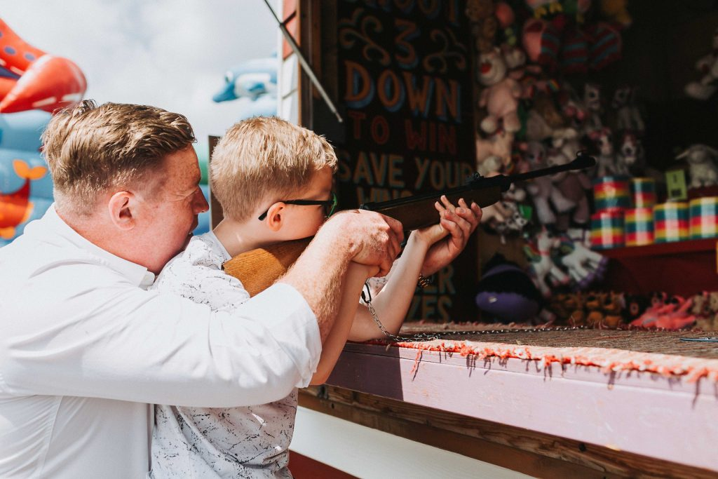 dad helping son at arcade shooting gallery on herne bay pier