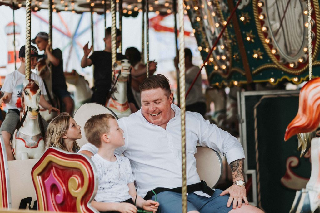 dad and son on carousel together smiling