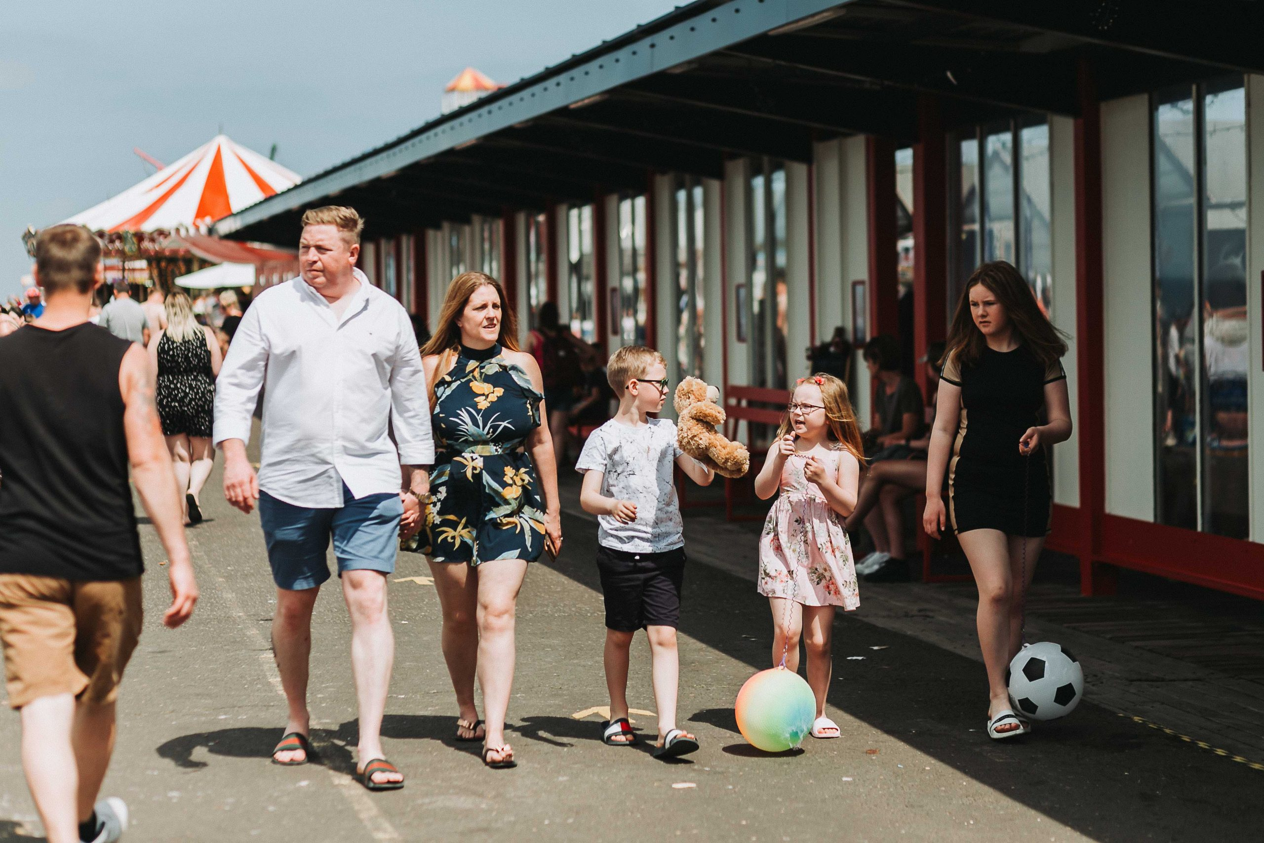 family walking on herne bay pier in the sunshine.